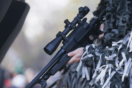 Details with the hands of an army sniper holding his rifle