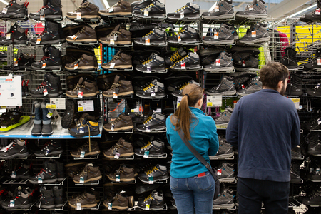 Bucharest, Romania - January 12, 2019: Customers in front of winter sneakers shelf in the French sporting goods retailer Decathlon, in Bucharest. Editorial