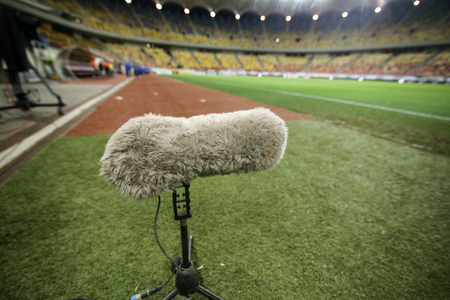 Hairy boom microphone on the grass of a soccer stadium