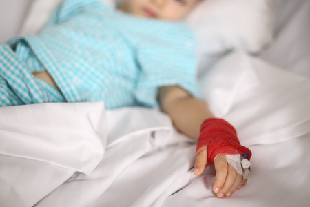 Details with a cannula on the hand of a ill little girl in a pediatric hospital reserve