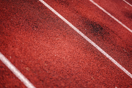 Details with the texture of a running track on a sunny day