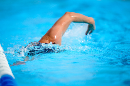 Details with a professional athlete swimming in swimming pool