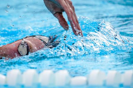 Détails avec un athlète professionnel nageant dans une piscine