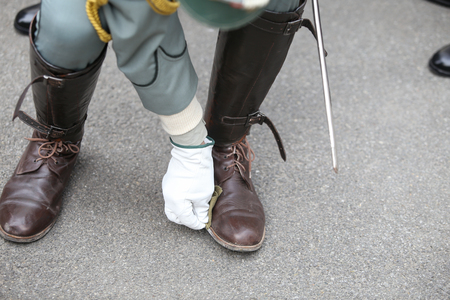 Details with a World War I reenactor soldier cleaning his leather boots