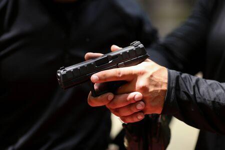 Detalles con las manos de un hombre que maneja una pistola de 9 mm. Foto de archivo