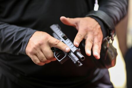 Details with the hands of a man handling a 9mm handgun