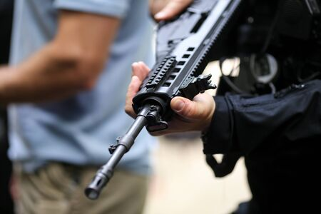 Details with the hands of a man holding an automatic rifle