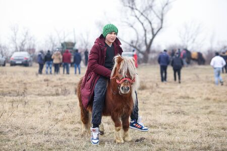 Pietrosani, Romania - January 6, 2019: Young boy is bareback riding a pony before an Epiphany celebration horse race.
