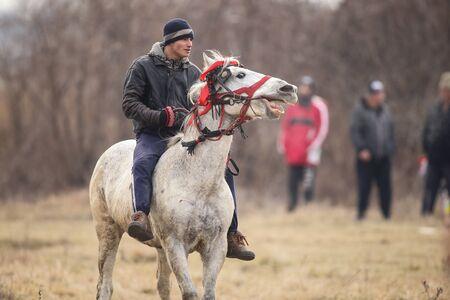 Pietrosani, Romania - January 6, 2019: Man is bareback riding an adorned horse before an Epiphany celebration horse race.
