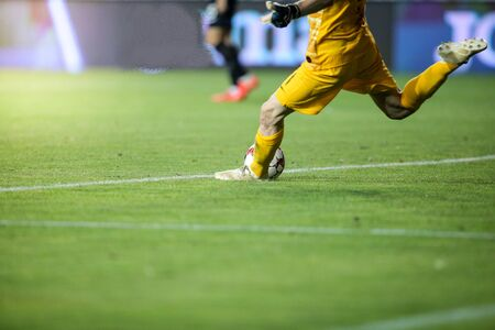 Details with the feet of a soccer goalkeeper kicking the ball during a match