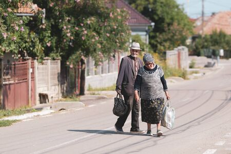 Bontida, Romania - July 21, 2019: An elderly couple on an empty street in a village in rural Romania on a hot bright summer day Редакционное