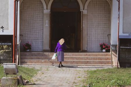 An old lady enters an christian orthodox church in a village in rural Romania 版權商用圖片