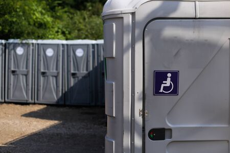 International Symbol of Access (Wheelchair Symbol) on a public toilet at a public event (music festival) Imagens
