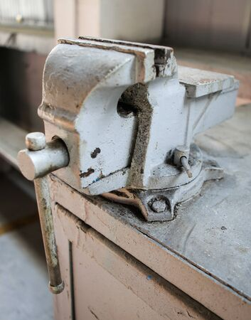 Shallow depth of field image with a rusty and dirty heavy iron vice on a workbench inside a workshop with no people around