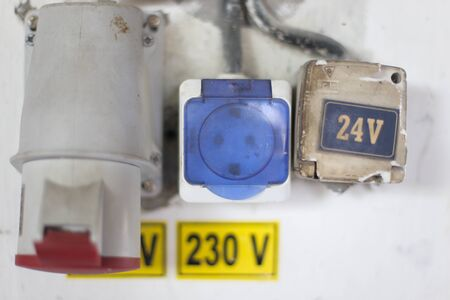 Worn out 400v, 230v and 24 industrial and multiphase power plugs and sockets on a dirty wall inside a workshop