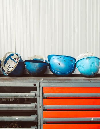 Dirty blue worker helmets on top of an old, rusty and dirty workbench in a workshop