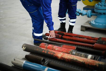 Details with the hands of a worker touching old and rusty heavy iron drilling equipment used in the oil and gas industry