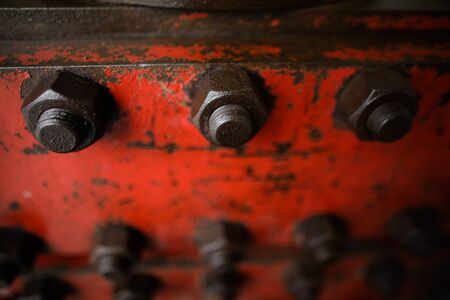 Shallow depth of field image with worn out heavy iron industrial equipment used in the oil and gas drilling industry (rusty bolts, nuts, pipes, levers)