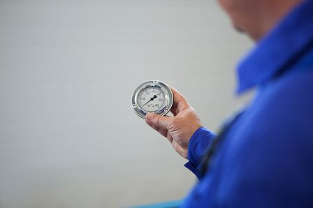 Details with the hand of a worker holding a broken glass PSI manometer