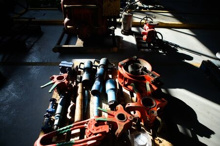 Shallow depth of field image with iron industrial equipment used in the oil and gas drilling industry laid on the ground of a workshop