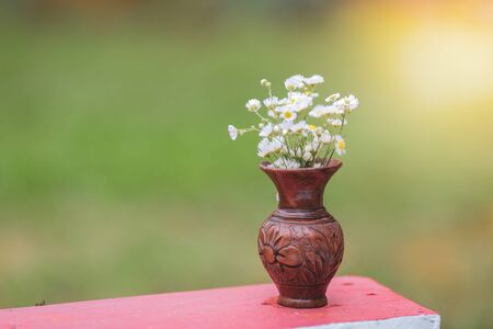 Shallow depth of field image with white wild flowers in a broken clay pot laid on a table corner