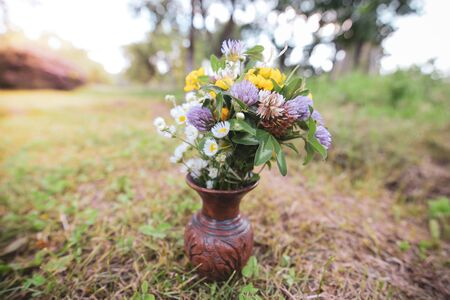 Bouquet of colorful wild wild flowers in a broken clay pot laid on the grass Imagens
