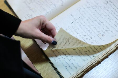 Details with the hands of a young woman reading an archive document