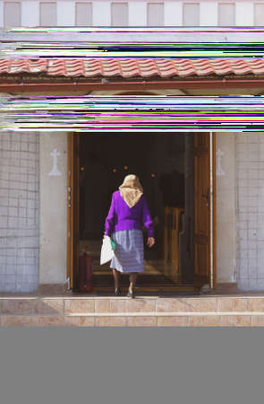An old lady enters an christian orthodox church in a village in rural Romania Editorial