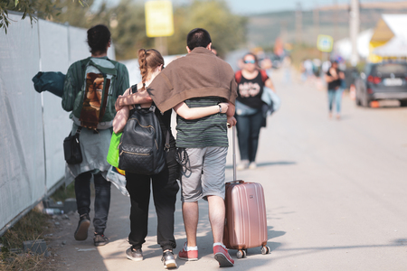 Teens going to the campsite of a music festival with their luggage, on a hot sunny summer day