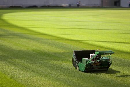 Industrial lawn mower machine on a soccer stadium with freshly installed and trimmed new turf