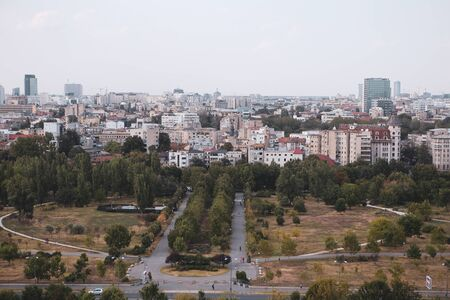 Cityscape of old part of Bucharest, with Izvor Park in the foreground, with many worn out buildings, as seen from the Palace of Parliament Archivio Fotografico - 129469837