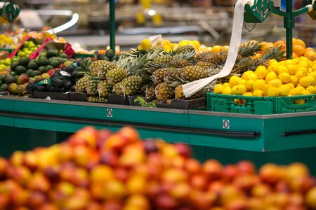 Pineapples and lemons on the fruits and vegetables aisle in a store.