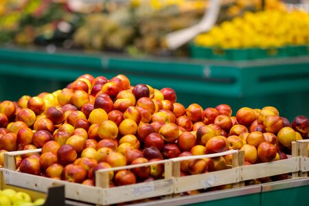 Nectarines on the fruits and vegetables aisle in a store.