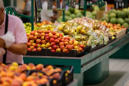 Red apples on the fruits and vegetables aisle in a store. Stock fotó