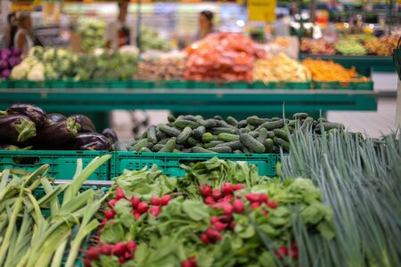 Cucumbers, eggplants, radish and spring onions on the fruits and vegetables aisle in a store.