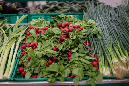 Radish and spring onions on the fruits and vegetables aisle in a store. Stock fotó