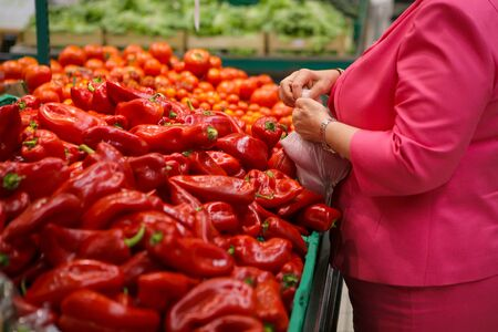 Woman choosing red sweet peppers on the fruits and vegetables aisle in a store. Stock fotó