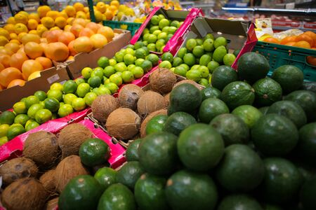 Coconuts, avocados, limes, grapefruits, oranges and mangos on the fruits and vegetables aisle in a store.
