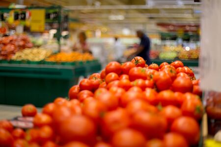 Shallow depth of field image with tomatoes on the fruits and vegetables aisle in a store