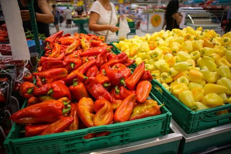 Red and yellow sweet peppers on the fruits and vegetables aisle in a store