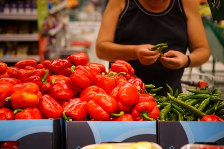 Details of a man choosing hot green peppers (sweet red peppers also on the shelf) on the fruits and vegetables aisle in a store Stock fotó