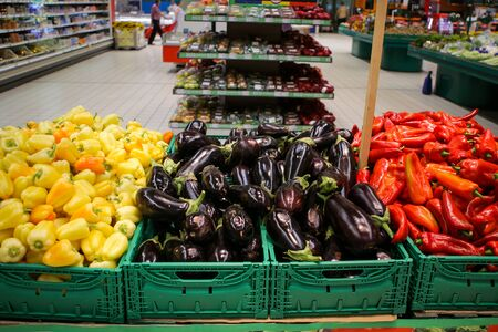 Red sweet peppers, eggplants and yellow sweet peppers on the fruits and vegetables aisle in a store Stock fotó