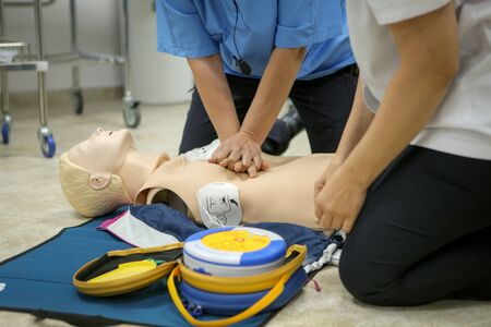 Woman medic demonstrates CPR methods on a plastic mannequin