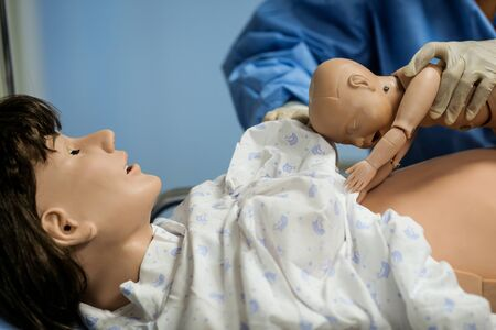 Details with plastic dummies representing a woman and her newly born baby used by medics and midwives for childbirth practice Stock fotó