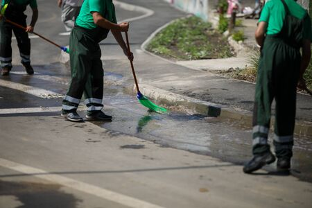 Street sweeper cleaning city sidewalk with water from a hose and a plastic broom - blue collar jobs 写真素材