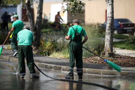 Street sweeper cleaning city sidewalk with water from a hose and a plastic broom - blue collar jobs Stock fotó