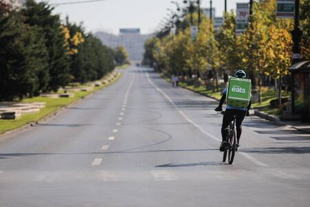 Bucharest, Romania - September 22, 2019: UBER Eats delivery biker on an empty boulevard during a sunny day.
