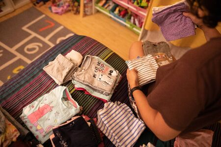 Shallow depth of field image with the hands of a mother rearranging her little daughter clothes
