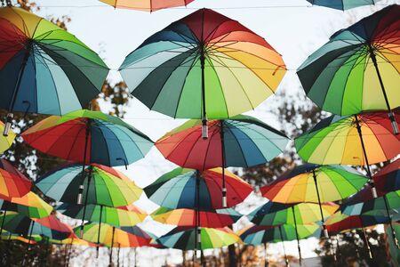Regenbogenfarbene Regenschirme hängen in einem öffentlichen Park Standard-Bild