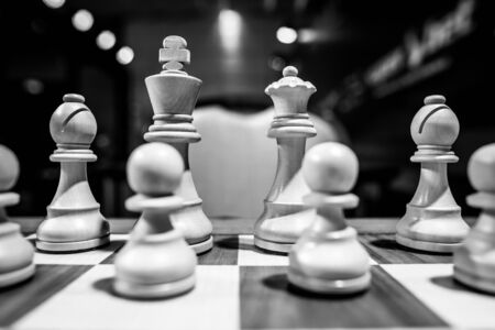 Monochrome shallow depth of field (selective focus) image with wooden chess pieces on a wooden table before a professional competition.